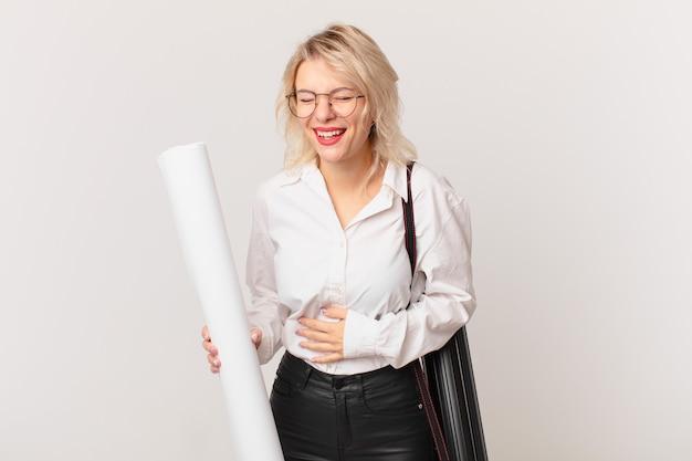 Молодая красивая женщина громко смеется над какой-то веселой шуткой. концепция архитектора
