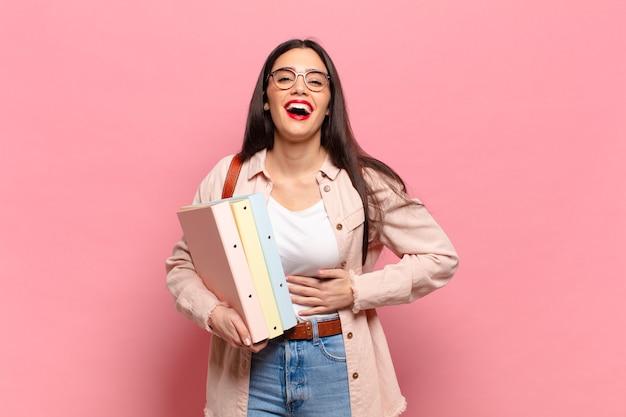 いくつかの陽気な冗談で大声で笑い、幸せで陽気に感じ、楽しんでいる若いきれいな女性。学生の概念