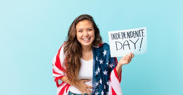 いくつかの陽気な冗談独立記念日の概念で大声で笑っている若いきれいな女性