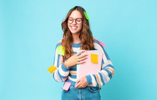 バッグを持って陽気な冗談を言って大声で笑い、本を持っている若いきれいな女性