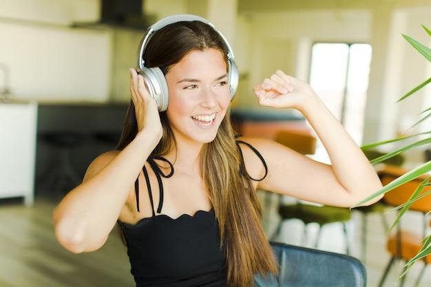 Молодая красивая женщина слушает музыку и танцует