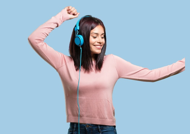 Young pretty woman listening to music, dancing and having fun, moving, shouting and expressing happiness, freedom concept