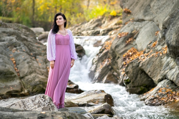 Young pretty woman in long fashionable dress standing near small mountain river with fast moving water.