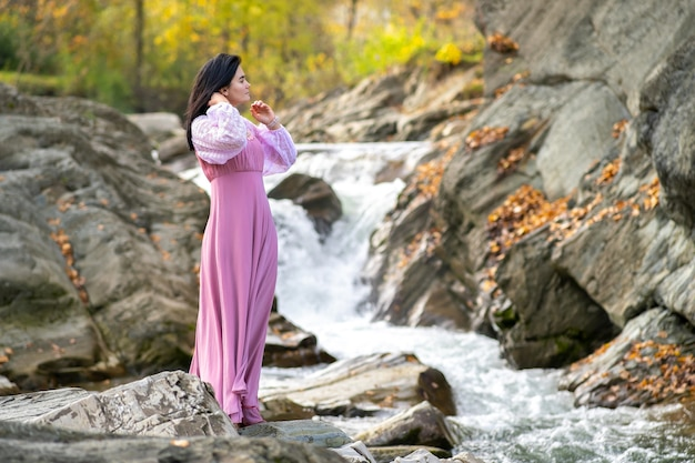 Young pretty woman in long pink fashionable dress standing near small river with fast moving water.