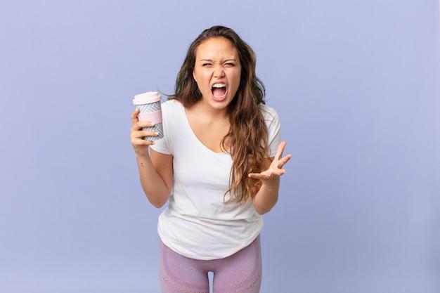 怒って、イライラして欲求不満に見え、コーヒーを持っている若いきれいな女性