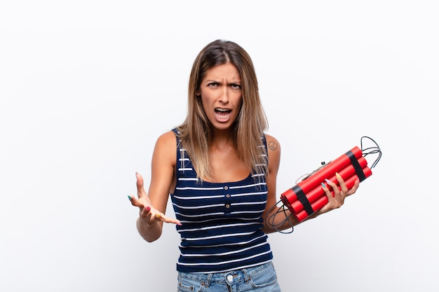 Молодая симпатичная женщина, выглядящая сердитой, раздраженной и расстроенной, кричащей или взволнованной динамитной бомбой
