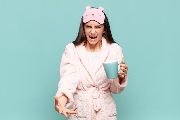 怒っている、イライラしている、欲求不満の叫び声のwtfまたはあなたの何が悪いのかを探している若いきれいな女性。パジャマのコンセプトを身に着けて目を覚ます