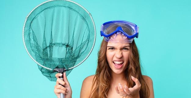 Молодая красивая женщина выглядит сердитой, раздраженной и разочарованной в очках и рыболовной сети