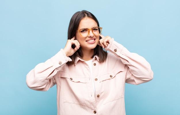 怒り、ストレス、イライラしているように見える若いきれいな女性は、耳をつんざくような音、音、または大音量の音楽で両耳を覆っています