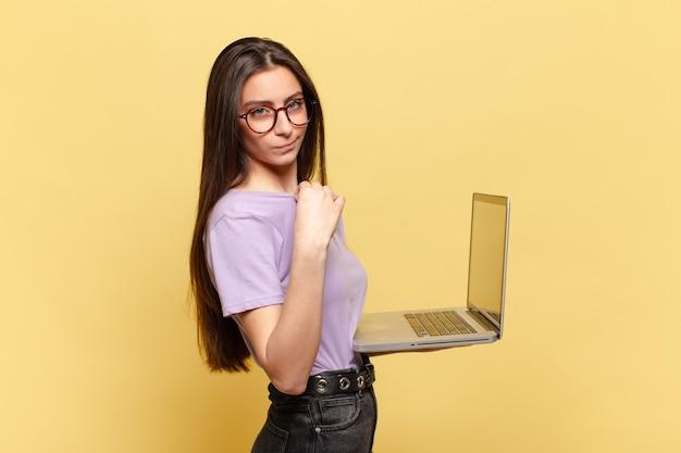 傲慢で、成功し、前向きで、誇りに思って、自己を指している若いきれいな女性。ノートパソコンのコンセプト