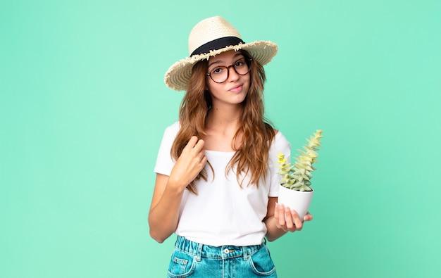 Молодая красивая женщина в соломенной шляпе, держащая кактус, выглядит высокомерной, успешной, позитивной и гордой.