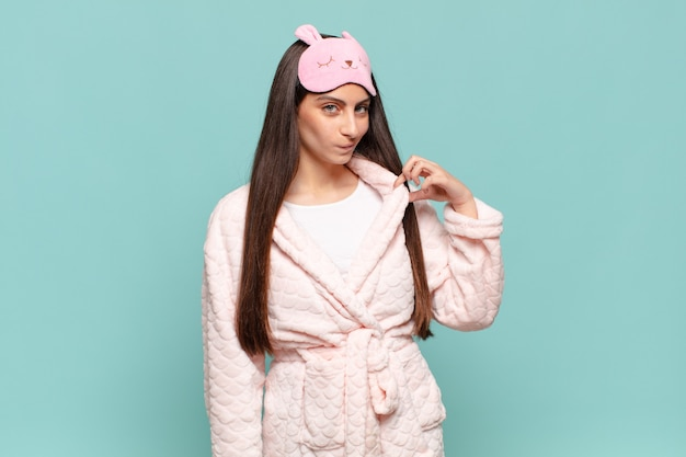 Young pretty woman looking arrogant, successful, positive and proud, pointing to self. awaking wearing pajamas concept