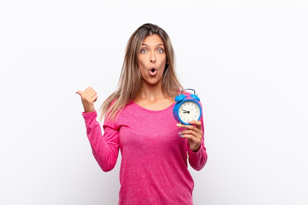 Young pretty woman looking astonished in disbelief, pointing at object on the side and saying wow, unbelievable holding an alarm clock.