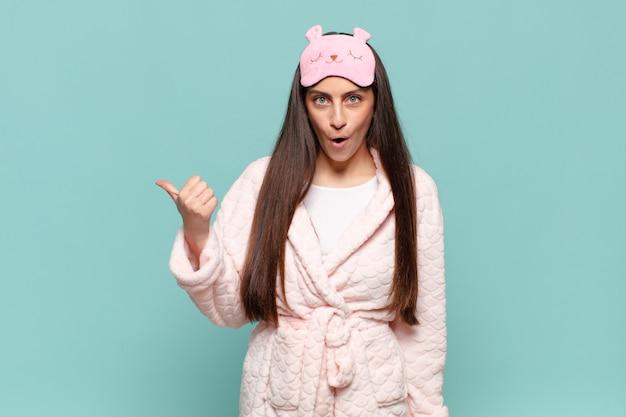 Молодая симпатичная женщина выглядела изумленной в недоумении, указывая на объект сбоку и говорила: «вау, невероятно». концепция пробуждения в пижаме