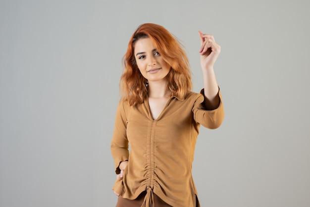 Молодая красивая женщина смотрит в камеру и держит руку