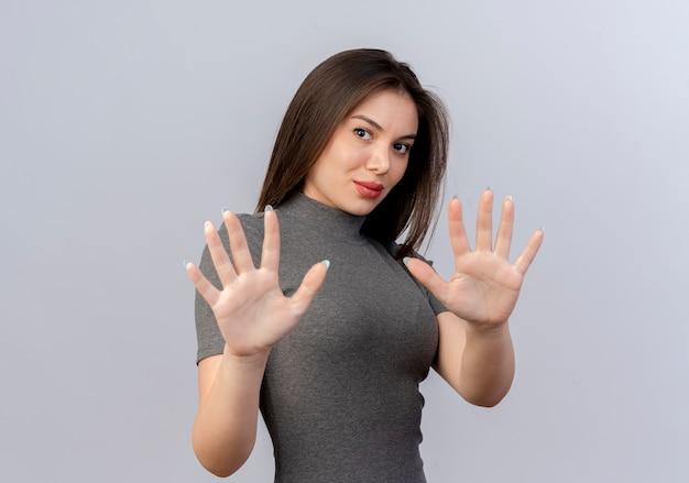 Молодая красивая женщина смотрит в камеру, протягивая руки, не делая никаких жестов в камеру, изолированную на белом фоне с копией пространства