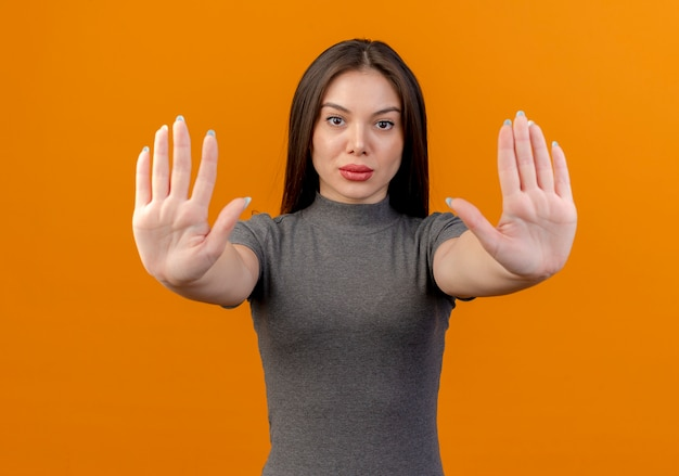 Young pretty woman looking at camera and gesturing stop isolated on orange background