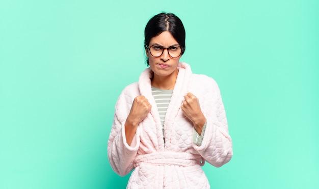 ボクシングの位置で戦う準備ができている拳で、自信を持って、怒って、強くて攻撃的に見える若いきれいな女性。パジャマのコンセプト