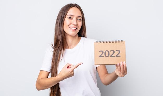 Молодая красивая женщина выглядит возбужденным и удивленным, указывая в сторону. концепция планировщика 2022 года