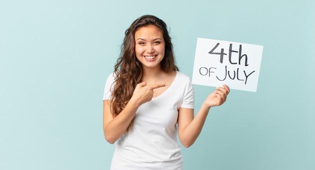 サイド独立記念日のコンセプトを指して興奮して驚いて見える若いきれいな女性