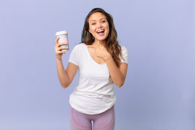 Young pretty woman looking excited and surprised pointing to the side and holding a coffee