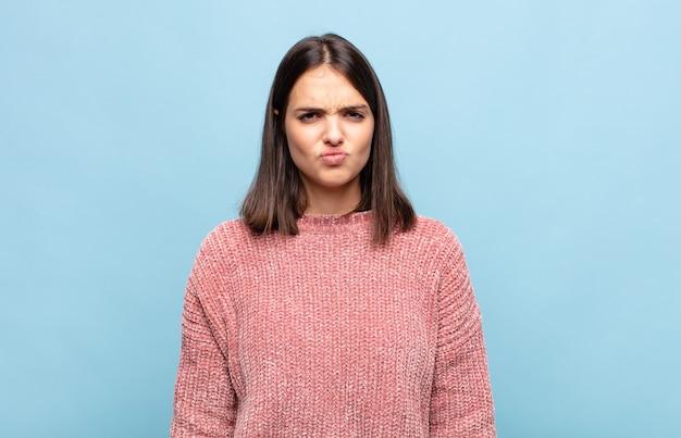 Молодая симпатичная женщина выглядит глупо и смешно с глупым косоглазым выражением лица, шутит и дурачится