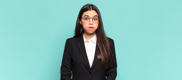 Young pretty woman looking goofy and funny with a silly cross-eyed expression, joking and fooling around. business concept