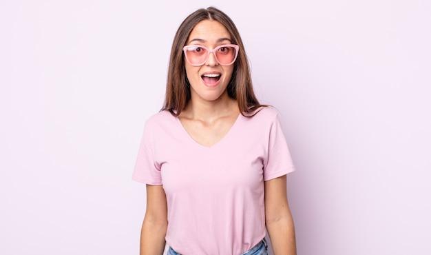 Молодая красивая женщина выглядит счастливой и приятно удивленной. концепция розовых солнцезащитных очков