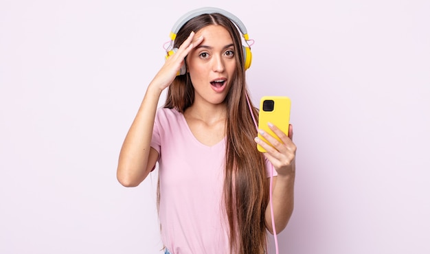 幸せに見えて、驚いて、驚いた若いきれいな女性。ヘッドホンとスマートフォン