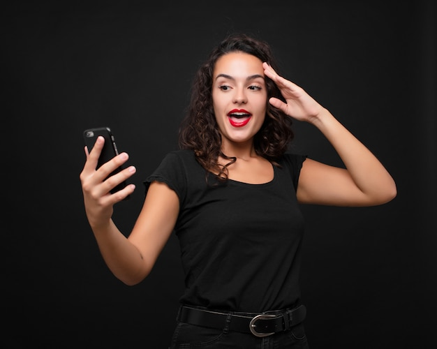 幸せ、驚き、驚き、笑顔、スマートフォンを保持している驚くべき信じられない良いニュースを実現している若いきれいな女性