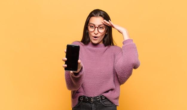 Молодая красивая женщина выглядит счастливой, удивленной и удивленной, улыбается и понимает удивительные и невероятные хорошие новости. концепция экрана телефона
