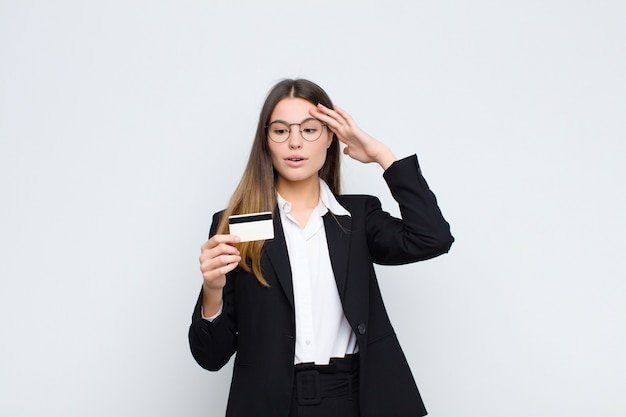 Молодая красивая женщина выглядит счастливой, удивленной и удивленной, улыбаясь и понимая удивительные и невероятные хорошие новости с помощью кредитной карты
