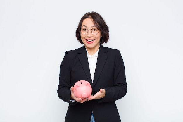 Young pretty woman looking happy and pleasantly surprised, excited with a fascinated and shocked expression with a piggy bank