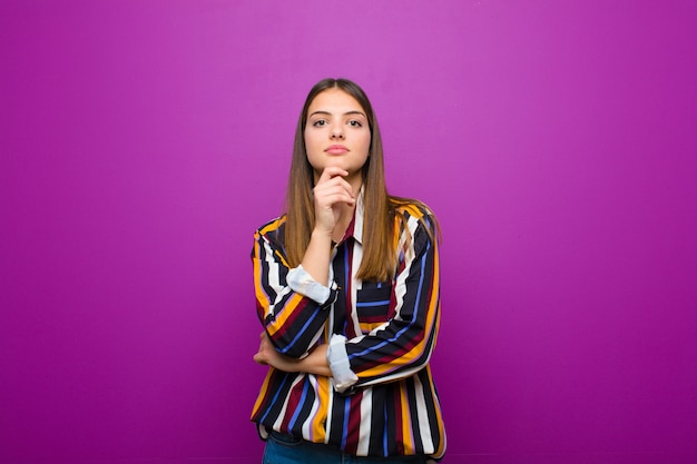 Young pretty woman looking happy and smiling with hand on chin, wondering or asking a question, comparing options over purple wall