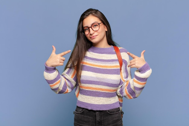 Молодая симпатичная женщина, выглядящая гордой, высокомерной, счастливой, удивленной и удовлетворенной, указывая на себя, чувствуя себя победителем. студенческая концепция