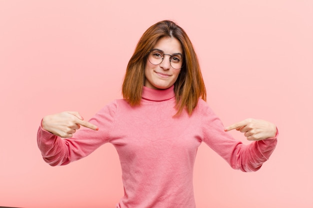 Young pretty woman looking proud, positive and casual pointing to chest with both hands against pink wall