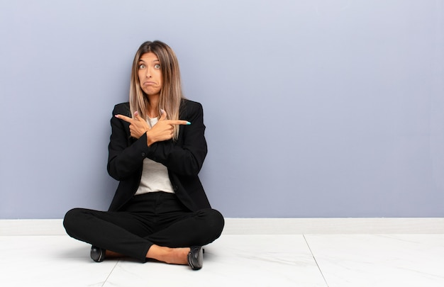 Молодая красивая женщина выглядит озадаченной и сбитой с толку, неуверенной в себе и указывающей в противоположных направлениях с сомнениями в бизнес-концепции