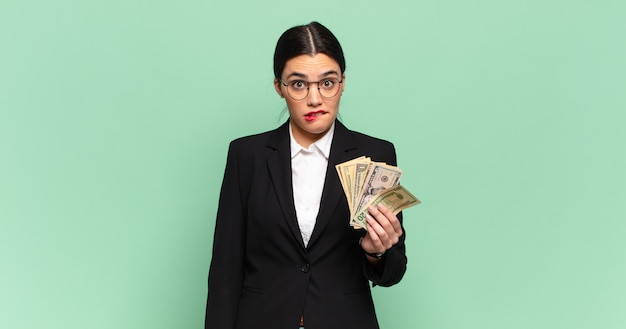 Young pretty woman looking puzzled and confused, biting lip with a nervous gesture, not knowing the answer to the problem. business and banknotes concept