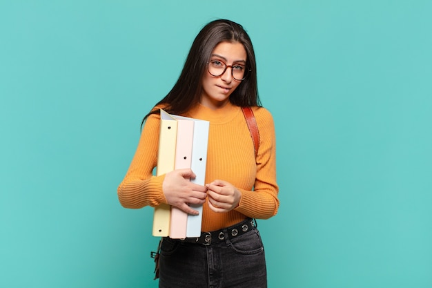 Young pretty woman looking puzzled and confused, biting lip with a nervous gesture, not knowing the answer to the problem. student concept
