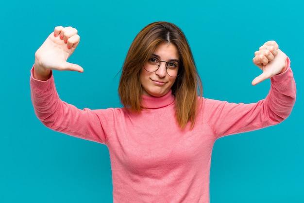 悲しい、失望したまたは怒っている探している若いきれいな女性、青い壁に不満を感じて不一致で親指を表示