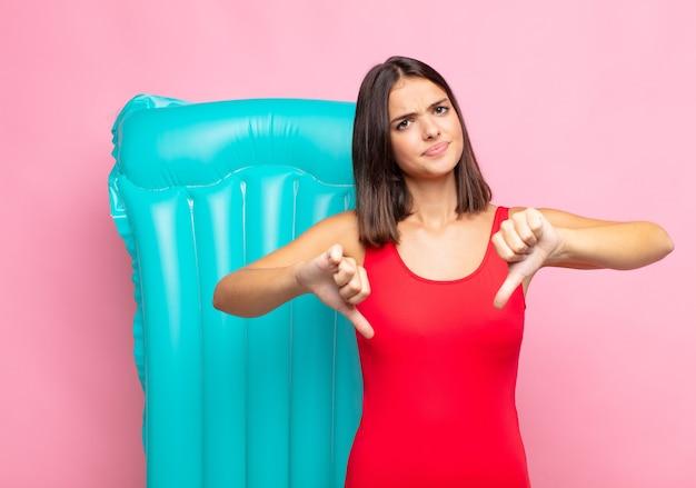 Молодая красивая женщина выглядит грустной, разочарованной или сердитой, показывает палец вниз в знак несогласия, чувствуя разочарование
