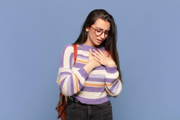 Молодая красивая женщина выглядит грустной, обиженной и убитой горем, держит обе руки близко к сердцу, плачет и чувствует себя подавленной. студенческая концепция