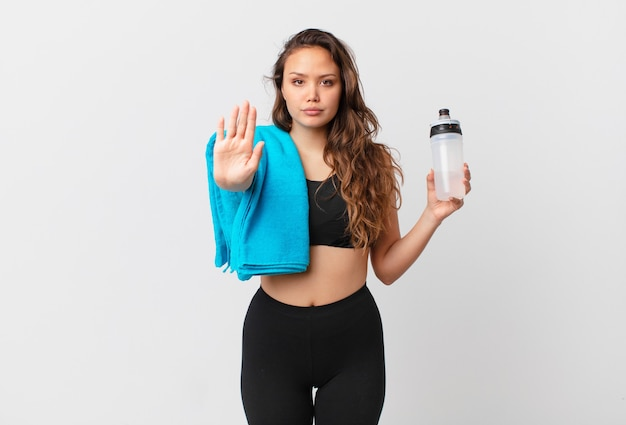 Young pretty woman looking serious showing open palm making stop gesture. fitness concept
