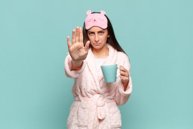 Молодая красивая женщина, выглядящая серьезной, суровой, недовольной и сердитой, показывает открытую ладонь, делая стоп-жест. концепция пробуждения в пижаме