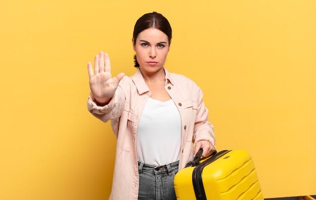 真面目で、厳しい、不機嫌で怒っている若いきれいな女性は、開いた手のひらを停止ジェスチャーを示しています