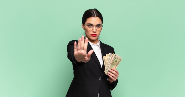 Young pretty woman looking serious, stern, displeased and angry showing open palm making stop gesture. business and banknotes concept