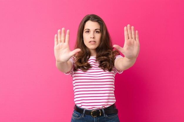 深刻な、不幸な、怒っていると不快なエントリを禁止またはピンクの壁に対して両方の開いた手のひらで停止を言っている若いきれいな女性