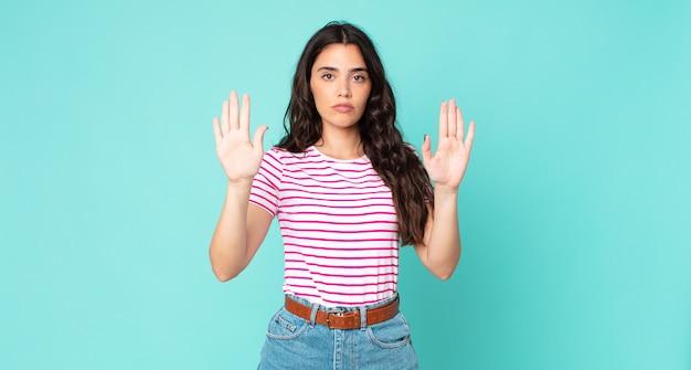 真面目で、不幸で、怒って、不機嫌そうな若いきれいな女性は、立ち入りを禁じているか、両方の手のひらを開いて停止すると言っています
