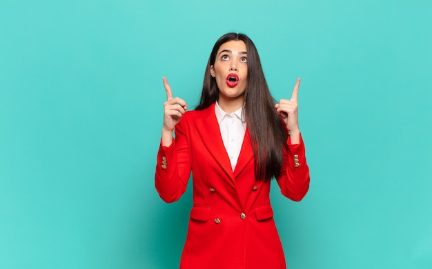 Young pretty woman looking shocked, amazed and open mouthed, pointing upwards with both hands to copy space. business concept