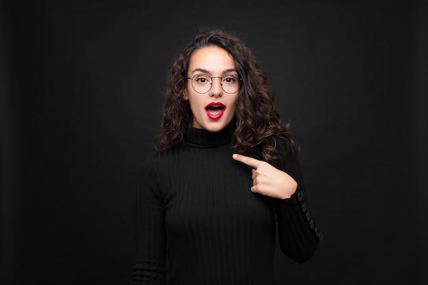 Молодая красивая женщина выглядит шокированной и удивленной с широко открытым ртом, указывая на себя у черной стены